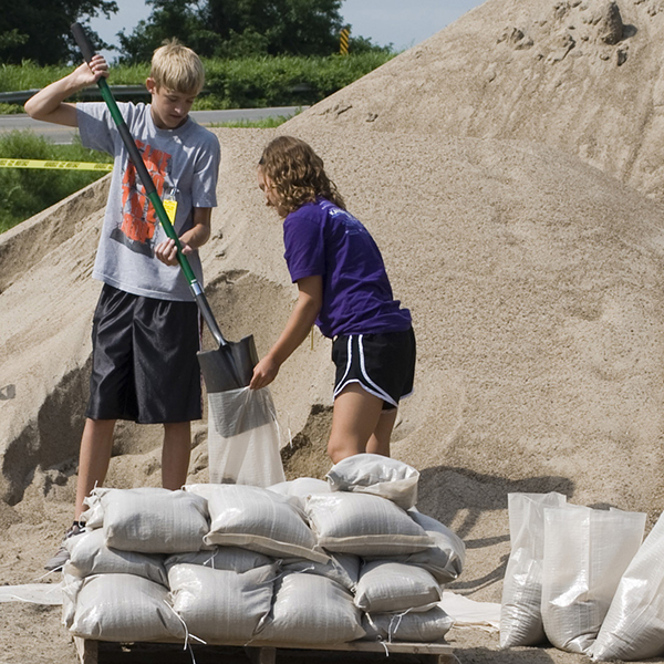 Photo of two kids filling sandbags on a sunny day.